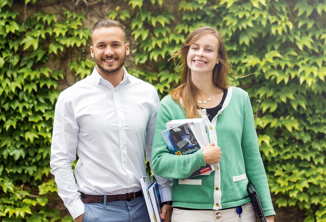 Zwei Studenten mit Büchern im Dualen Studium Informatik