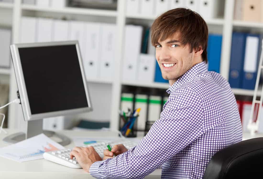 Lächelnder junger Mann am PC als Darstellung für Fachinformatiker