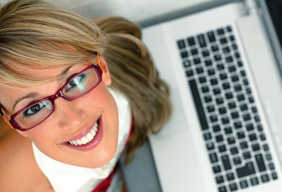 Junge Kauffrau mit Brille lächelt in die Kamera